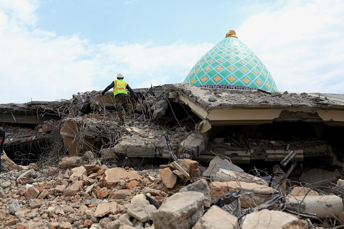 A rescuer searchers for victims feared to be buried under the rubble of Jamiul Jamaah Mosque in Pamenang village, North Lombok, on Wednesday Aug. 8, 2018. JP/Seto Wardhana