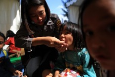 A police officer feeds a child victim during a Trauma Healing Program at a shelter in Supersemar field in Tanjung District, North Lombok. The propgram was aimed at helping children cope with trauma from the natural disaster. JP/Seto Wardhana