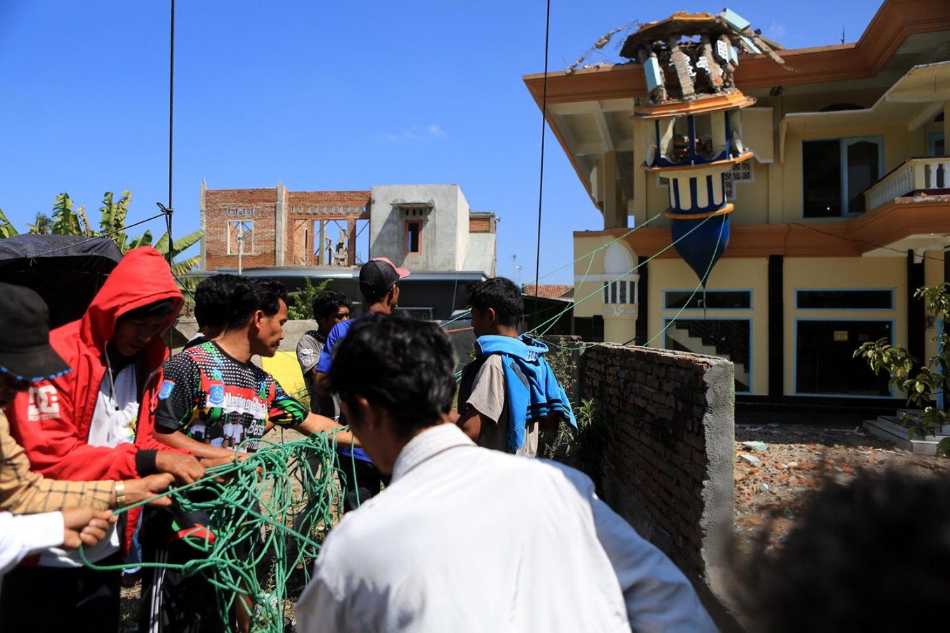 Villagers try to pull a minaret at Al Ihsan Mosque, which was damaged by an earthquake in Batu Layar, West Lombok, on Aug. 8, 2018. JP/Seto Wardhana