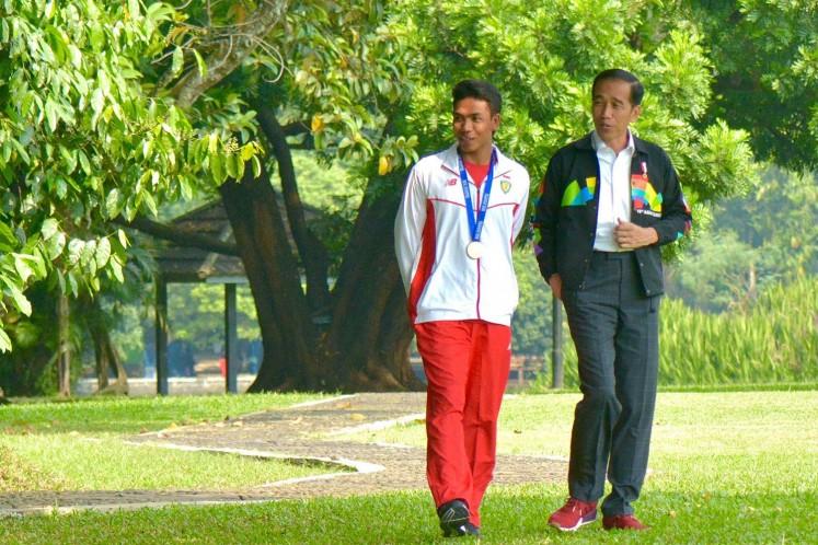 Young sprinter Lalu Muhammad Zohri (left) walks with President Jokowi.