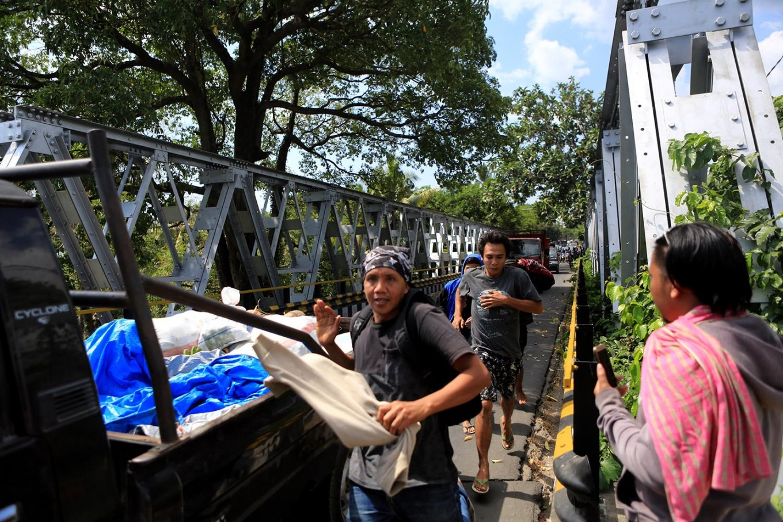 Citizens run along a bridge after another 6.2-magnitude aftershock strikes North Lombok on Thursday Aug. 9, 2018. JP/Seto Wardhana