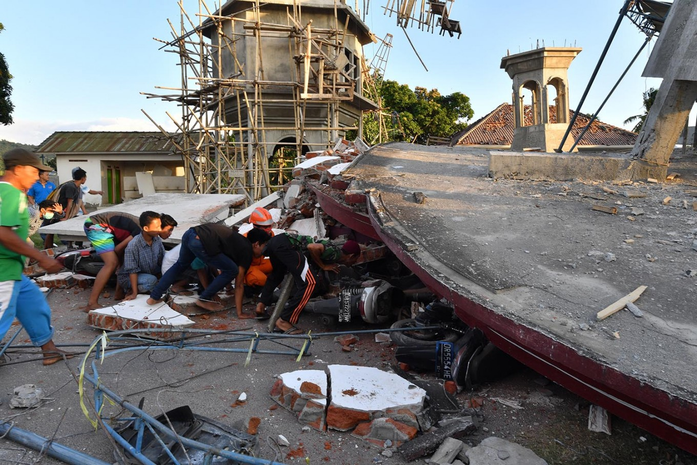 Residents and a search and rescue team member look under the ruins of a mosque in Pemenang, North Lombok, on Aug. 6, 2018, the day after a 6.9-magnitude earthquake struck the area. AFP/Adek Berry
