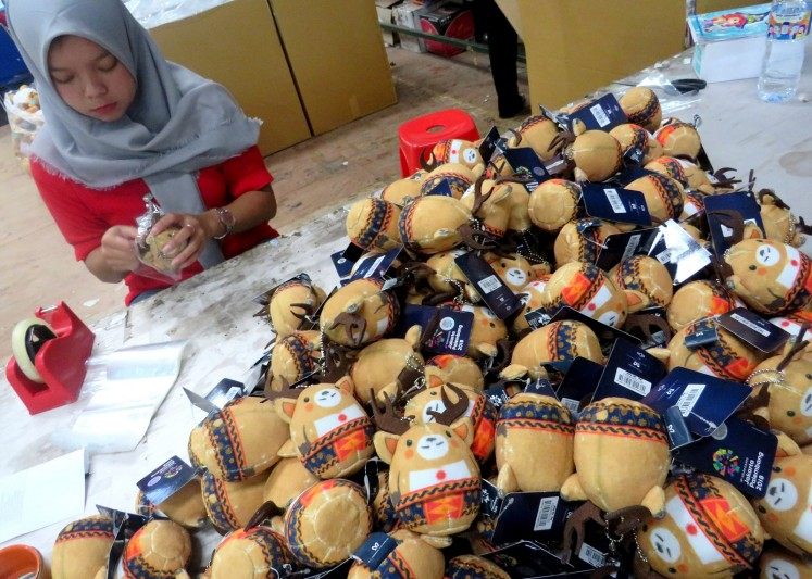 An employee of Istana Boneka packs dolls of Atung the Bawean deer at the company's factory in Malang, East Java, on Friday, Aug. 10, 2018.