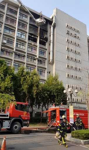 This photograph by Taiwan agency CNA Photo taken on August 13, 2018 shows firetrucks outside a nine-storey hospital in New Taipei City after battling a fire at a hospice that broke out on the seventh floor (top C). Nine people were killed and 15 injured in a blaze that broke out early on August 13 at the hospice for the terminally ill, near Taiwan's capital Taipei, fire officials said.