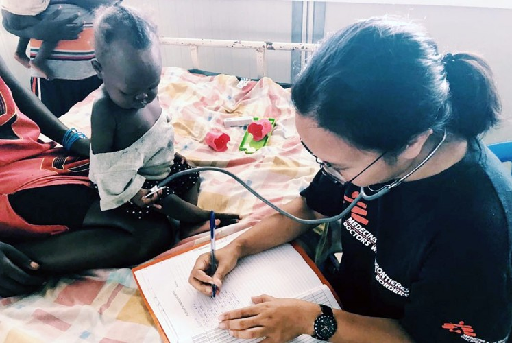 At work: Rangi Wirantika writes information about a patient in South Sudan.