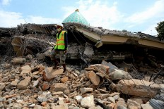 In ruins: A search and rescue officer stands on the rubble of a collapsed building following a series of tremors that have hit Lombok, West Nusa Tenggara, since July 29. JP/ Seto Wardhana