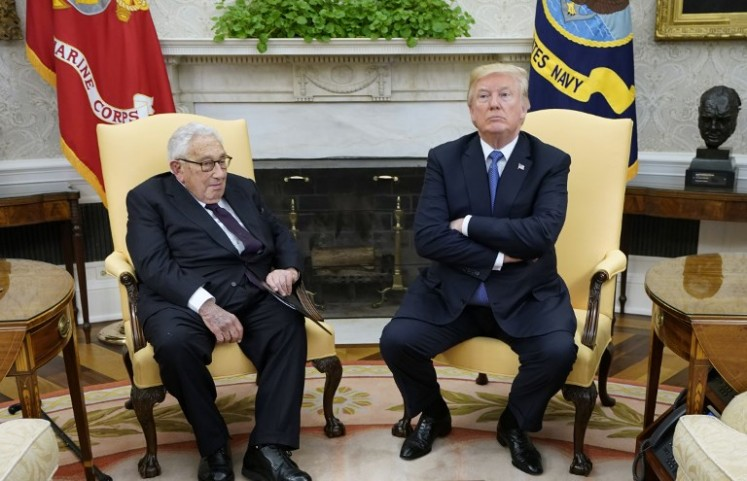 US President Donald Trump (right) meets with former US Secretary of State Henry Kissinger in the Oval Office of the White House on October 10, 2017 in Washington, DC.