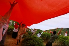 Students and citizens hand-in-hand hoist the giant flag. JP/Maksum Nur Fauzan