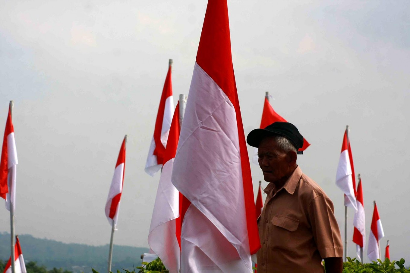 Decorating Mount Cilik with red-and-white flags