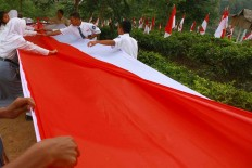 Students prepare to hoist the giant flag of 100 meters long and 3 meters wide. JP/Maksum Nur Fauzan
