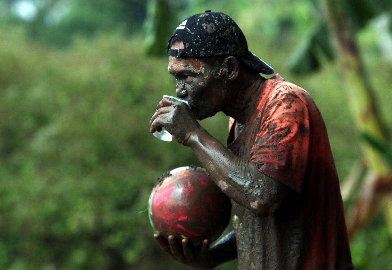 A player with his face covered in mud drinks a glass of water. JP/Boy T. Harjanto