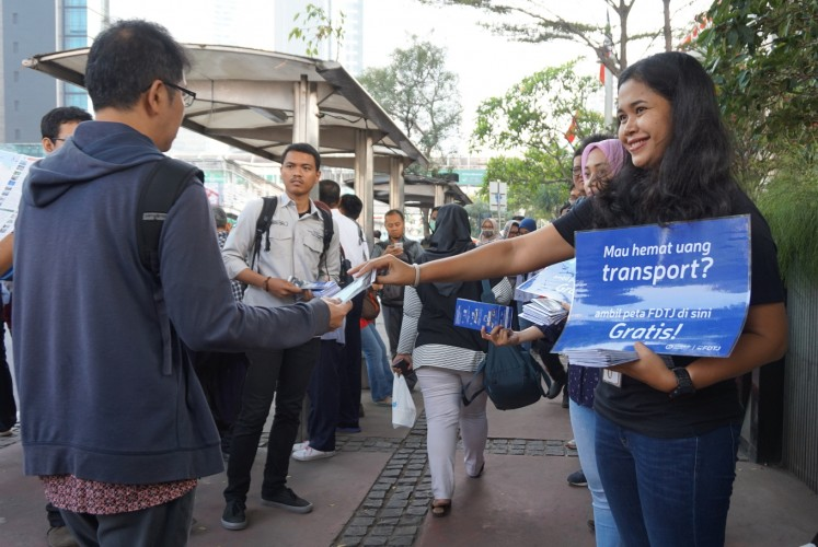 Sharing is caring: A member of the FDTJ hands out the 'Public Transportation Map and Guide' to commuters in Central Jakarta.