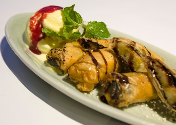 'Piscok goreng' is deep-fried banana wrapped in filo pastry with chocolate sauce and a scoop of vanilla ice cream.