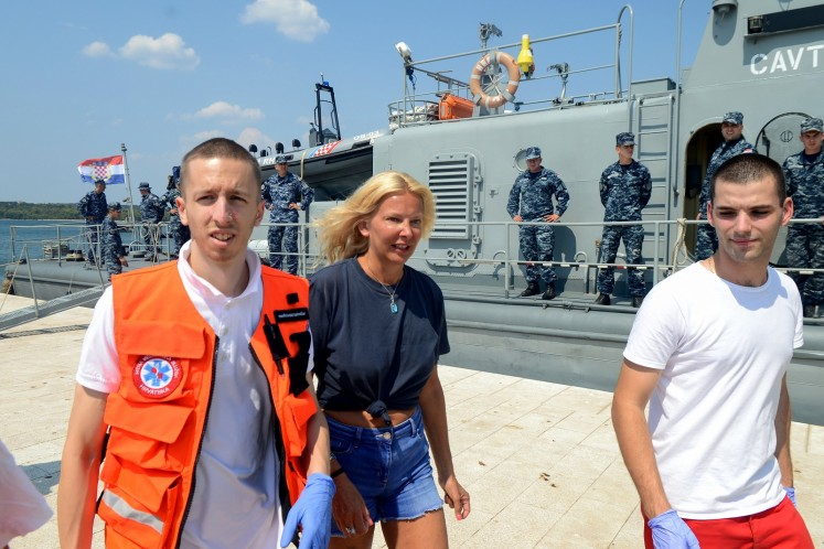 British tourist Kay Longstaff (C) exits Croatia's coast guard ship in Pula, on August 19, 2018, which saved her after falling off a cruise ship near Croatian coast.