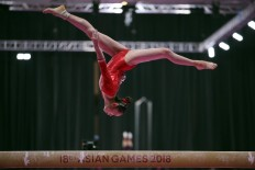 Grace under pressure: Chinese gymnast Liu Tingting performs during the artistic gymnastics competition. JP/ PJ Leo