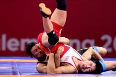 Get a grip: Kyrgyztan wrestler Kanybek Zholcubekov (left) controls his opponent from the People's Republic of Korea during men's Greco-Roman wrestling match. JP/ Seto Wardhana