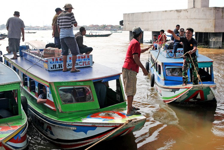 River ride: A boat trip on the 750-kilometer Musi River is one of Palembang's tourism highlights. Unfortunately, the river's natural beauty is barely visible and pollution has turned its waters a murky brown color.