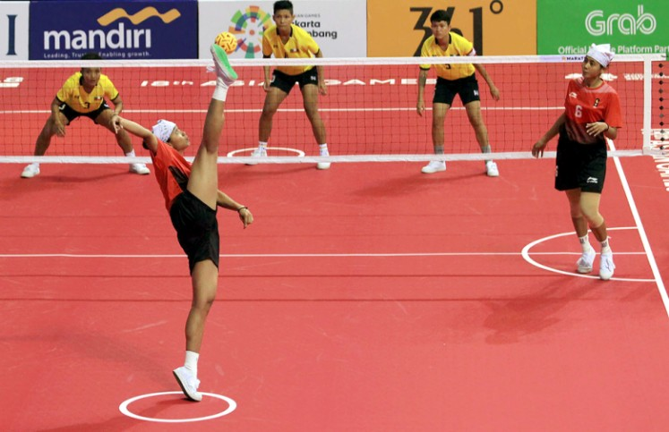 Indonesia's Leni (left) kicks the ball while her twin sister Lena (right) looks on during their sepak takraw women's team regu match against Myanmar in the 2018 Asian Games at Ranau Hall in Jakabaring Sports City in Palembang, South Sumatra on Aug. 19.