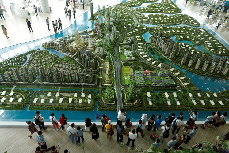 Prospective buyers look at a model of the development at the Country Gardens' Forest City showroom in Johor Bahru, Malaysia February 21, 2017. REUTERS/Edgar Su/File Photo
