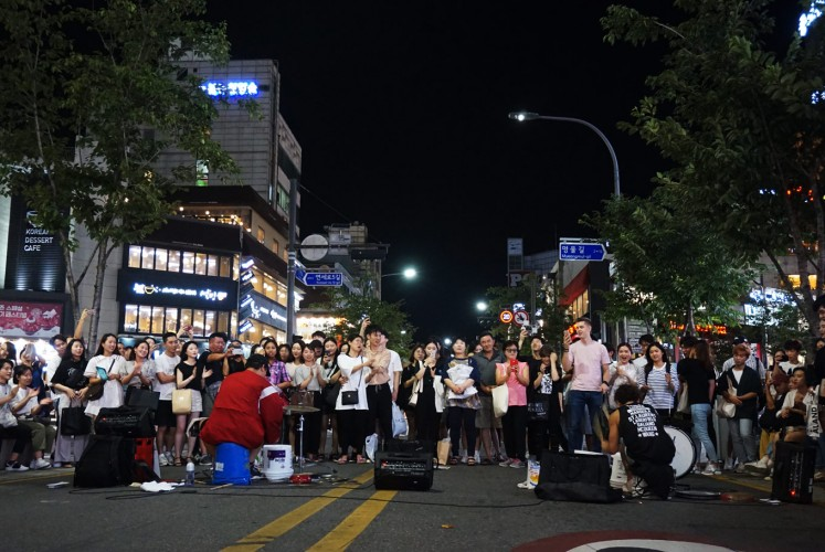 Visitors watch a music performance by street artists in Yonsei-ro.