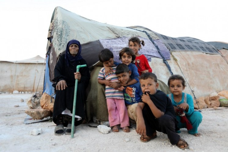 An elderly woman and children sit in front of a tent in a camp for the displaced from Idlib's southern province and Hama's northern provice, in Kafr Dariyan situated at a short distance from Syria's border with Turkey, on August 26, 2018.  OMAR HAJ KADOUR / AFP