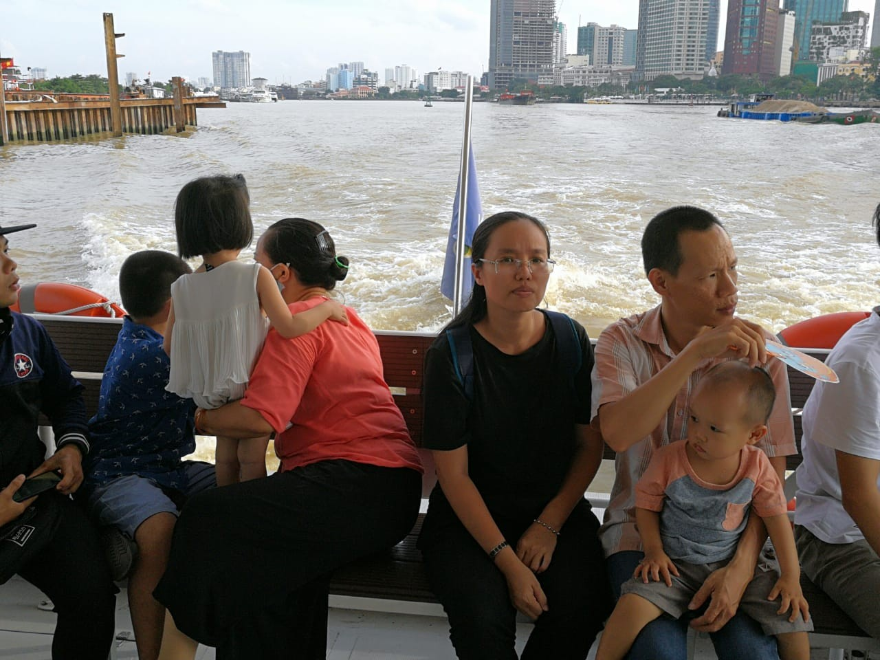 Tourists enjoy scenery from the rear deck of the Saigon water bus.
