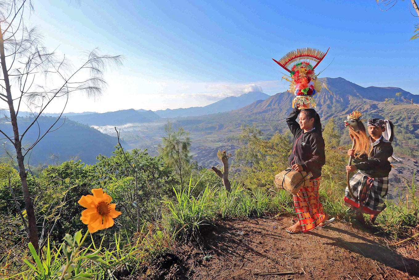 En-route: Two performers of the sacred Sanghyang Jaran dance walk along a hilly path on the slope of Mount Batur. The picture was captured by Kochiana.