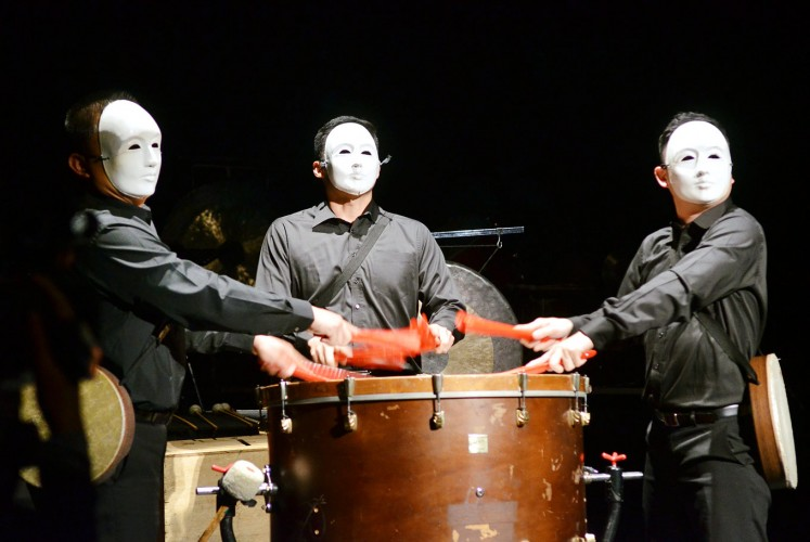 "Masks on: Three Ju Percussion Group musicians in white masks beat the Chinese bass drum with red folding fans in order to perform Chang Chiung-Ying's ""Solar Myth"" piece."