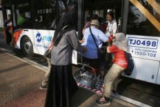 Volunteers help a person with disability on to a shuttle service in Jakarta. JP/Dhoni Setiawan