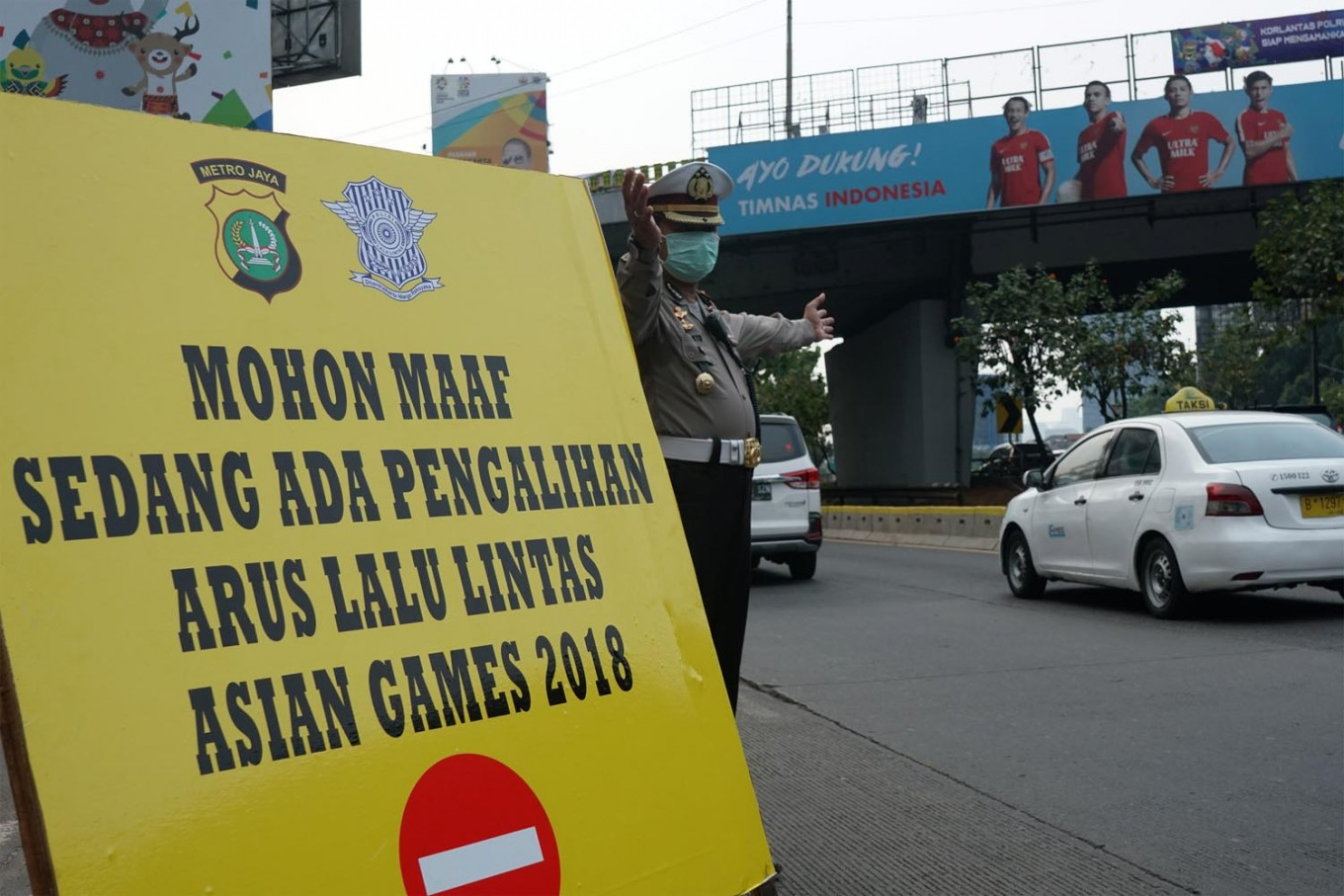 A police officer gives direction to motorists following to road restriction ahead of the Games closing ceremony in Jakarta. JP/Umair Rizaludin