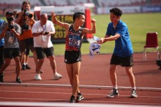 An official hands a bottled water to Japan's Hiroto Inoue after the finish line in Jakarta. JP/P.J. Leo