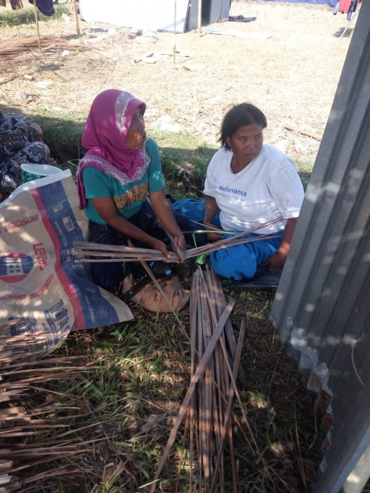 Earthquake survivors weave palm leaves into roof panels for their temporary houses on Lombok Island, West Nusa Tenggara.