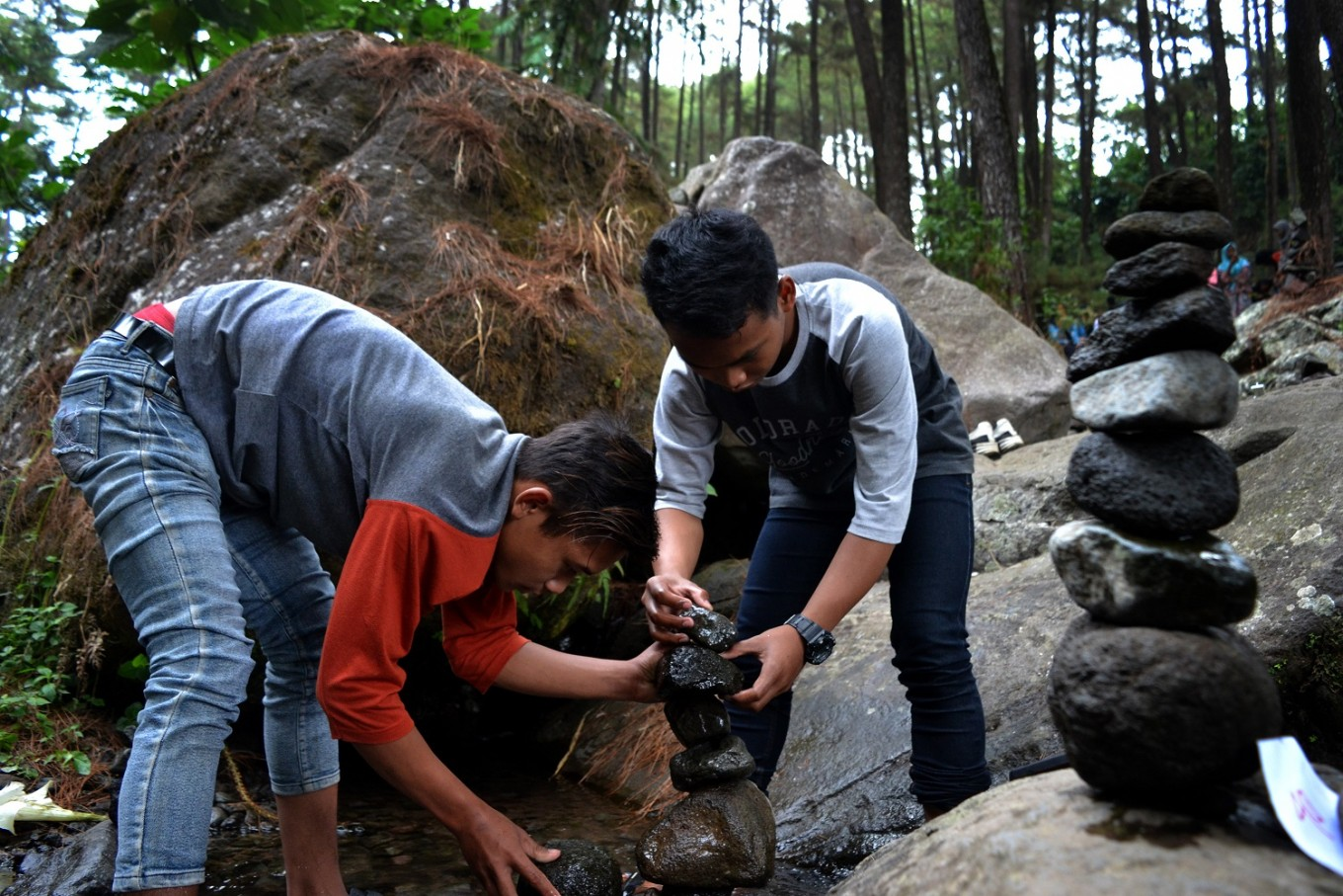 Tourists take part in a rock balancing activity during the third installment of the Earth Gravity Festival.