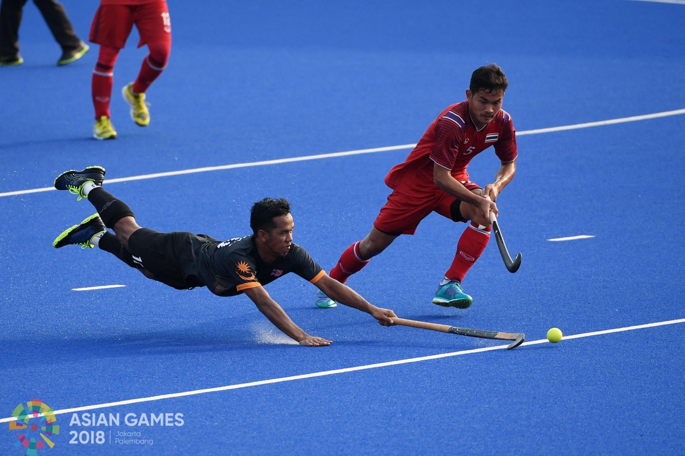 Malaysia's Faizal Saari (L) and Thailand's Boonmee (R) fight for the ball during the men's hockey pool B match between Malaysia and Thailand at the 2018 Asian Games in Jakarta on August. 22.Inasgoc via Antara/ Dhoni Setiawan