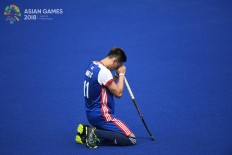 Hong Kong men's hockey player Ka Chun Chan kneels before a preliminary hockey game against South Korea at the 2018 Asian Games at the Hockey Field in the Gelora Bung Karno (GBK) sport complex in Jakarta on Monday, Aug. 20. Inasgoc via Antara/ Dhoni Setiawan