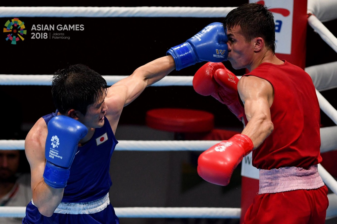 Japanese boxer Arashi Morisaka (left) attacks Hursand Imankuliyev of Turkmenistan in a men's 60-kilogram match at the 2018 Asian Games at the Jakarta International Expo in Kemayoran, Central Jakarta, on Friday, August. 24. Inasgoc via Antara/Wendra Ajistyatama
