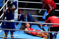 Filipino boxer Mario Fernandez (center) is treated by a doctor after being knocked down by Jaafar A Al Sudani of Iraq (left) during a 56 kg fight at the 2018 Asian Games at the Jakarta International Expo in Kemayoran, Central Jakarta, on Saturday, August. 25. Inasgoc via Antara/ Wendra Ajistyatama