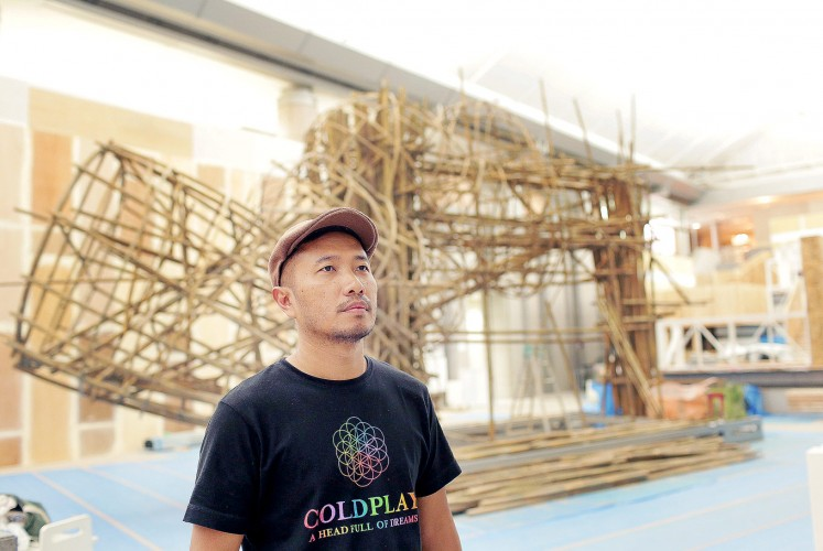 Work in progress: Artist Joko Dwi Avianto poses with his artwork for the exhibition at the center of Yokohama Museum of Art's Grand Gallery in Japan.