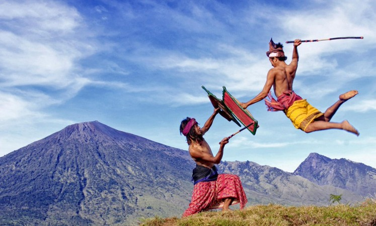 Fighting spirit: Two Lombok men in West Nusa Tenggara engage in the local martial art of peresean, where they fight one another using sticks and protect themselves with rattan armor.