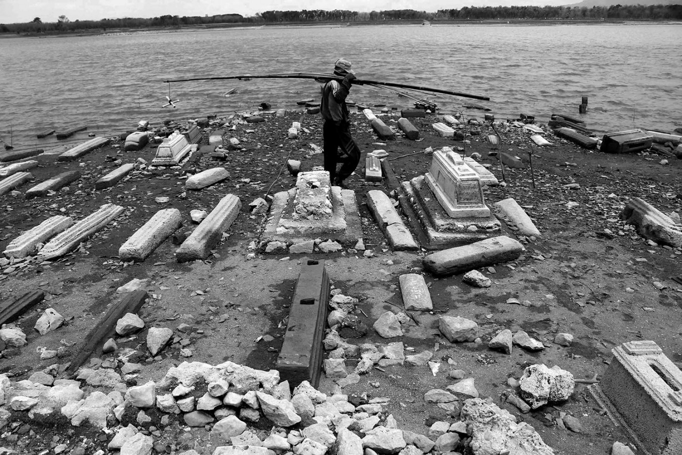 A villager carries his fishing rod, passing graves at the former area of Kenteng village in the Gajah Mungkur dam area. JP/Maksum Nur Fauzan