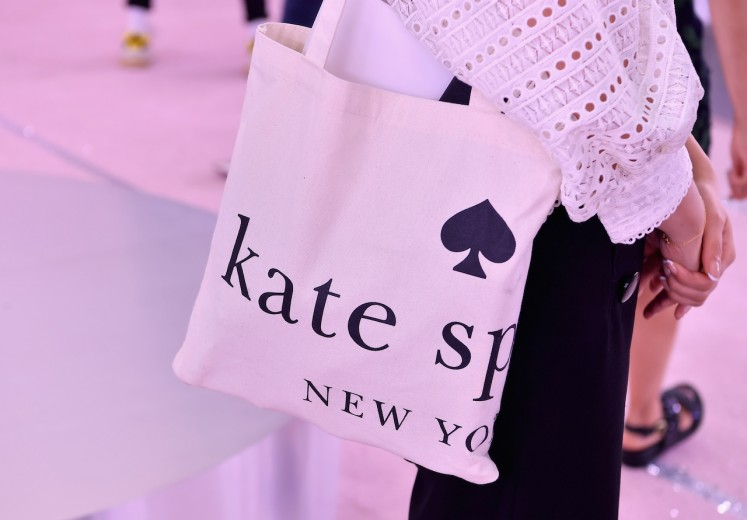 A guest wears a Kate Spade bag during the Kate Spade New York Fashion Show during New York Fashion Week at New York Public Library on September 7