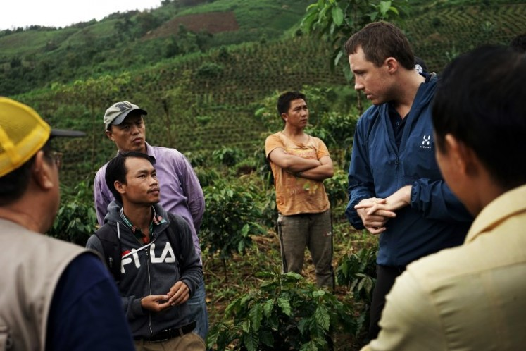 Erlend Falch (R) from the UN Office on Drugs and Crime conferring with local officals at a coffee plantation in Houaphan province, northern Laos. Wedged between five countries, reclusive Laos has for decades played a starring role in the