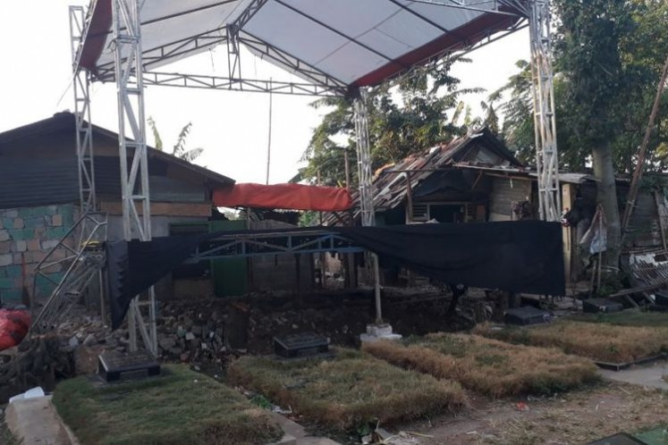 The photo shows the stage used for a circumcision celebration party that was erected near the Pondok Kelapa Public Cemetery in East Jakarta.