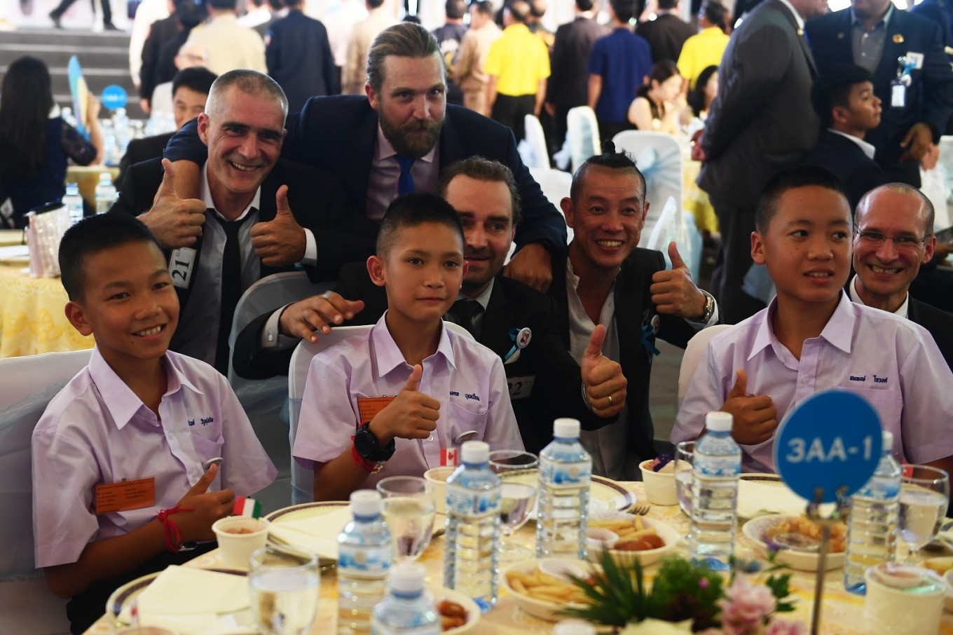Three members of the 'Wild Boars' football club pose with divers, who were involved in their rescue operation, during a reception in Bangkok on September 6, 2018 | AFP