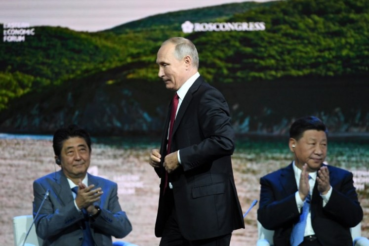 China's President Xi Jinping (R), Japan's Prime Minister Shinzo Abe (L) and Russian President Vladimir Putin attend the plenary session of the Eastern Economic Forum in Vladivostok on September 12, 2018.  Kirill KUDRYAVTSEV / AFP
