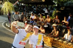 Musical sideline: Two runners pose for a selfie in front of a traditional Balinese orchestra during the 2018 Maybank Bali Marathon on Sept. 9 in Gianyar, Bali. The international race also seeks to promote Balinese culture.