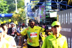 A splash of energy: A runner enjoys a splash of cold water as he completes his course at the 2018 Maybank Bali Marathon on Sept. 9 in Gianyar, Bali.
