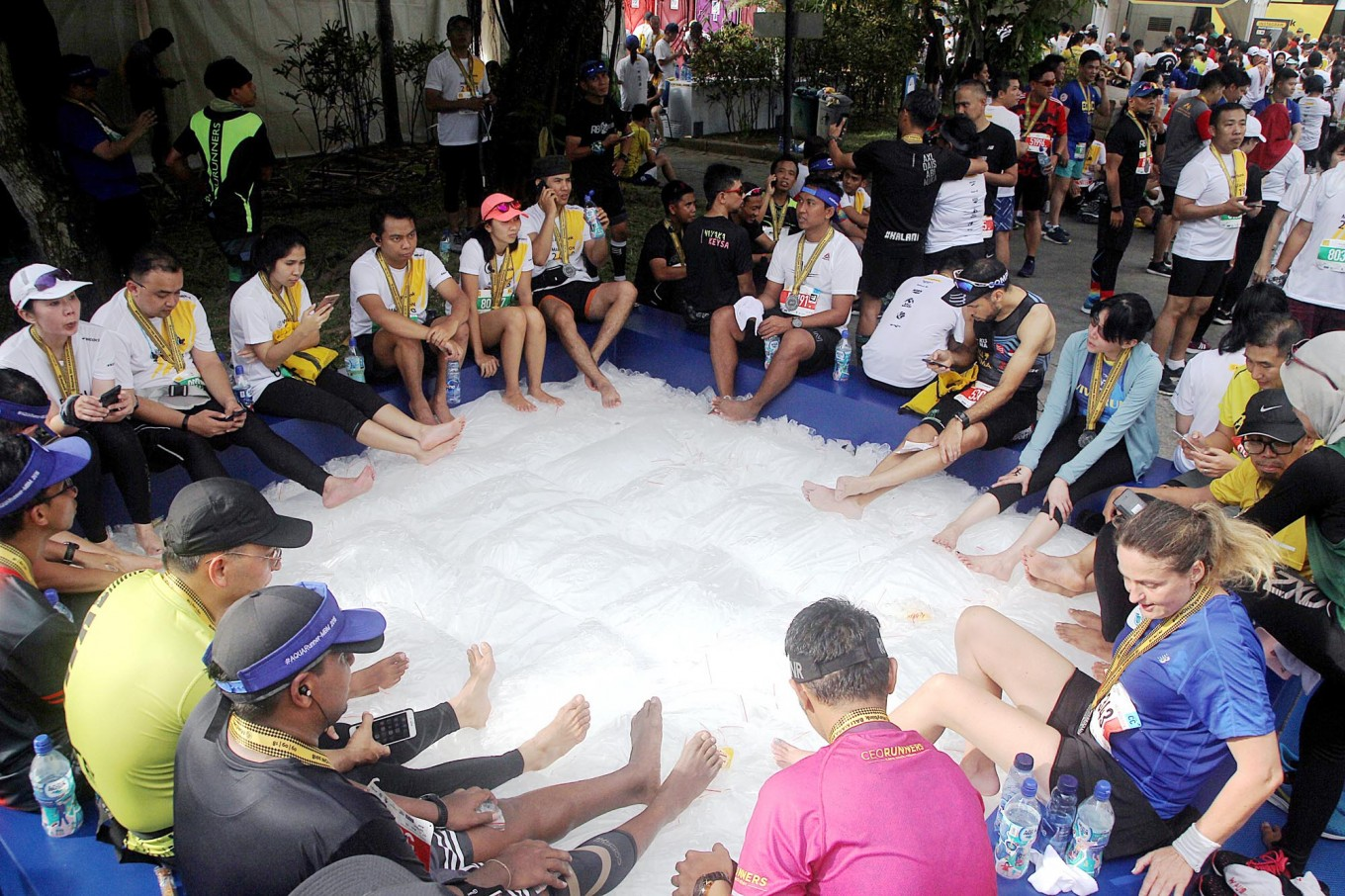 Cooling down: Runners lay their feet on ice cubes to reduce aches and stiffness upon completing the 2018 Maybank Bali Marathon on Sept. 9 in Gianyar, Bali.