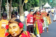 A cultural touch: A 2018 Maybank Bali Marathon runner pauses to take a photograph with a local performer wearing a mask depicting a Balinese shadow puppet character in Gianyar, Bali. The race showcases a variety of Balinese music and dance performances to entertain runners throughout the track.