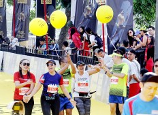 We did it!: Amateur runners cheer upon completing their course in the 2018 Maybank Bali Marathon on Sept. 9 in Gianyar, Bali. Besides earning a medal, these runners also derive satisfaction from knowing that they possess the endurance and determination required to finish the race.